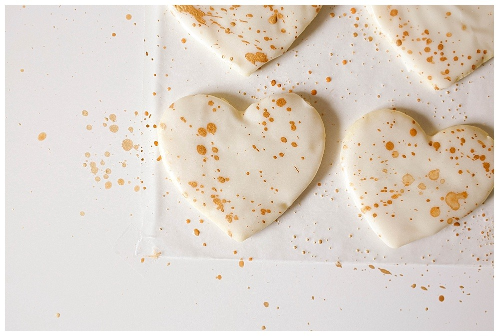 Lavender Vanilla Bean Sugar Cookies Recipe by The Wood and Spoon Blog by Kate Wood and Abby Hollar of The Hollardays Blog. This is a simple recipe for homemade cutout sugar cookies flavored with dried lavender and vanilla bean paste. The icing is simple and dries quick and doesn't require a piping bag or tip like Royal icing. The gold lustre luster dust is mixed with alcohol to create a shiny metallic paint that you can splatter on your cookies with a basting brush. Find the tutorial and how to paint cookies on thewoodandspoon.com