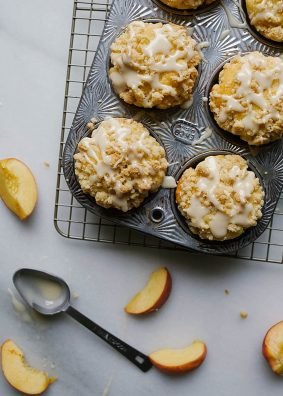 Peach Crumb Muffins Recipe By The Wood and Spoon Blog by Kate Wood. These are moist, fluffy, vanilla butter muffins filled with chunks of fresh peaches. These muffins are tall and I'll give you my tips on how to get a domed muffin every time! They are topped with a sweet and salty brown sugar streusel crumble and a dripped vanilla glaze. Find the recipe for these summer treats - the perfect breakfast or brunch item- on the blog. Thewoodandspoon.com summer fruit, beach recipes, southern muffins