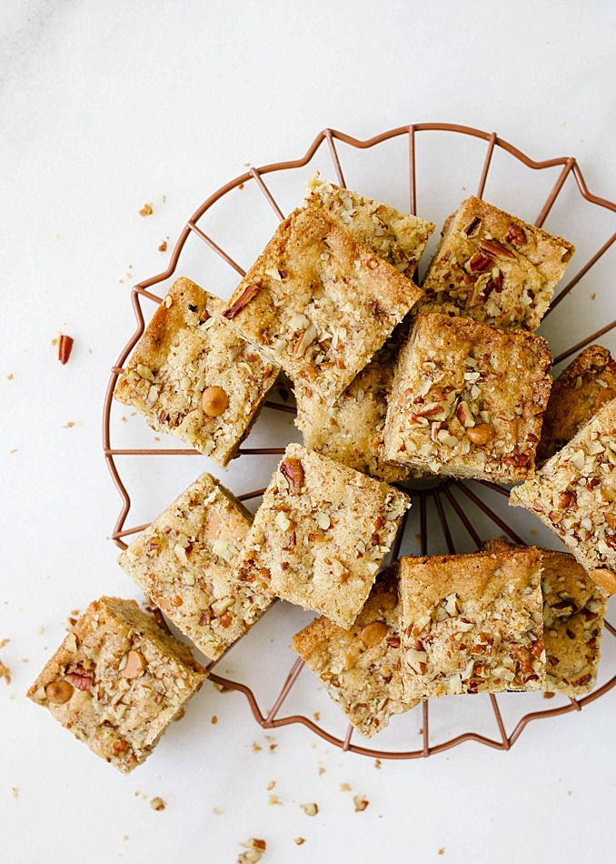 Butterscotch Blondies by the Wood and Spoon blog by Kate Wood. These are simple rich, and easy blondies made with brown sugar, pecans, and butterscotch chips. The caramel taste in these bars are crowd pleasers and perfect for sharing with a group of people. The recipe bakes quickly in a brownie pan and can be frozen and made ahead. Find the recipe for these nutty blondies on thewoodandspoon.com