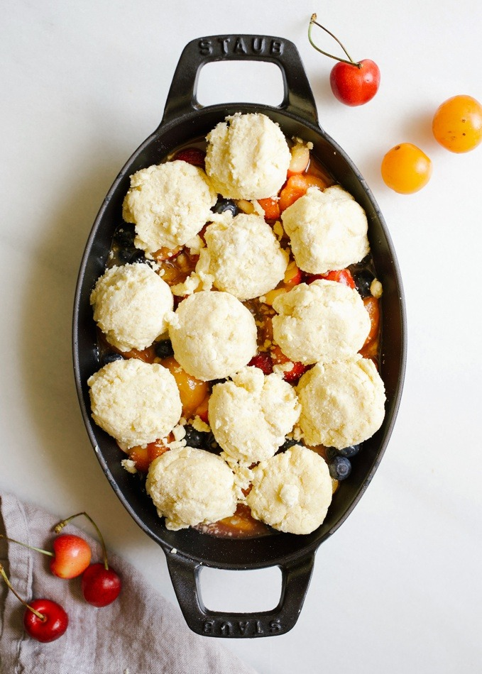 Stone Fruit Skillet Cobbler recipe by Wood and Spoon. This is a simple summer fruit dessert fit for any of your favorites- peaches, plum, berries, nectarines, cherries, etc! The topping is a biscuit / scone like topping scooped on top with cornmeal and butter. It's a simple make ahead dish that will let your summer produce shine. Find the recipe and how to on thewoodandspoon.com by Kate wood.