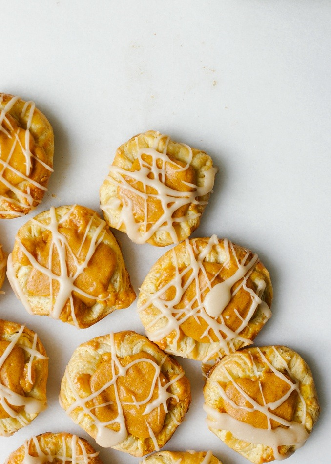 Pumpkin Danishes Recipe by Wood and Spoon. These are fluffy buttery pastries with a simple pumpkin filling and a brown butter glaze. Each danish is small and each batch makes enough to share with a crowd. These are flavored with fall spices and make a really special autumn breakfast baked good. Find the recipe and how to for these danishes on thewoodandspoon.com by Kate Wood.