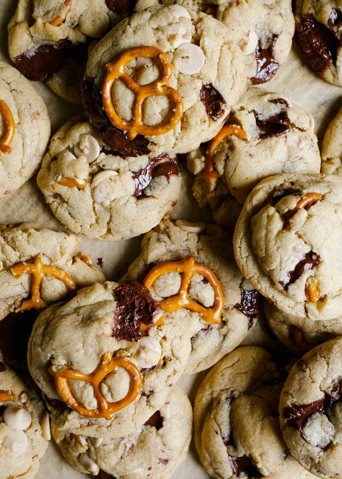 Peanut butter caramel pretzel chocolate chip cookies recipe. These are chewy peanut butter cookies with pretzel twists, chocolate chunks, and caramel bits. These are sweet and salty treats perfect for the holidays, Christmas, Thanksgiving, or cookie exchanges. Find the giant chewy gooey cookies on thewoodandspoon.com by Kate wood