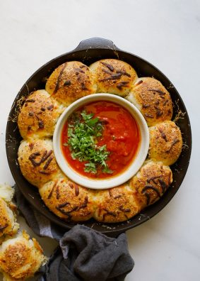Cheesy Dinner Rolls with Tomato Dipping Sauce recipe by wood and spoon. These are soft and fluffy yeast rolls filled with gooey mozzarella cheese. Baked in a skillet and topped with italian herbs and cheese, these rolls serve as a great appetizer, side dish, and more! Make your holiday bread bowls extra delicious with these stuffed yeast breads! Check it out on thewoodandspoon.com