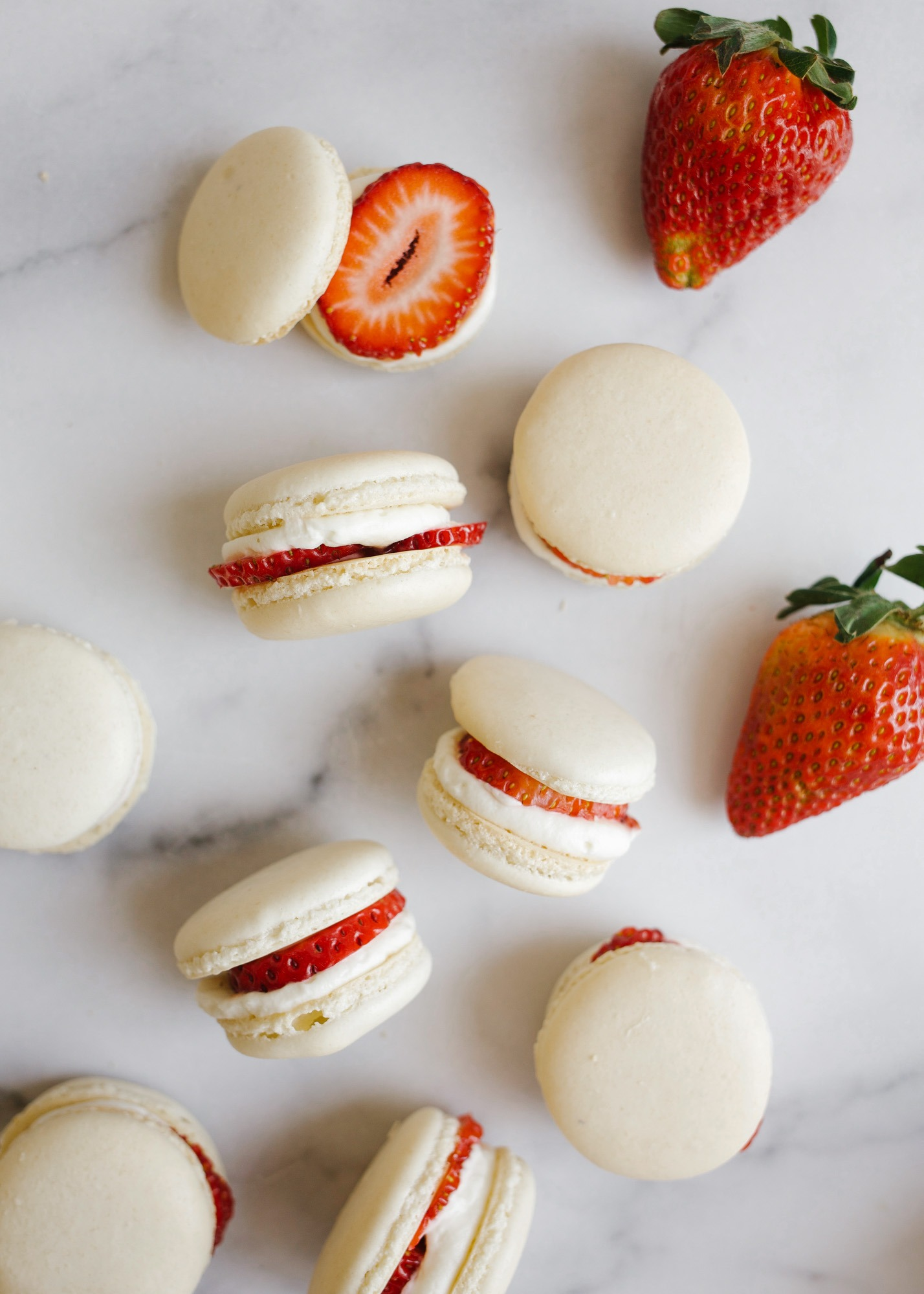 Strawberry Shortcake Macarons and Mother's Day gift guide by wood and spoon. These are simple homemade macarons filled with whipped cream, strawberry jam, and fresh fruit. These taste like a shortcake in cookie form. Gifts for mom's on your list including cookbook, jewelry, beauty and home supplies, and more. Read all about these fancy spring desserts and learn how to make them on thewoodandspoon.com