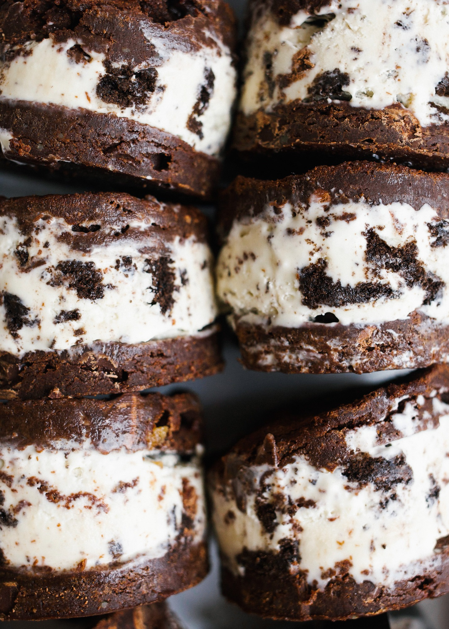 Brownie Ice Cream Sandwiches by Wood and Spoon blog. These are soft baked brownies stuffed with a no churn cookies and cream Oreo ice cream filling. The brownies stay chewy when frozen and this recipe makes a batch to feed a crew. Learn how to make homemade frozen treats without an ice cream maker on thewoodandspoon.com