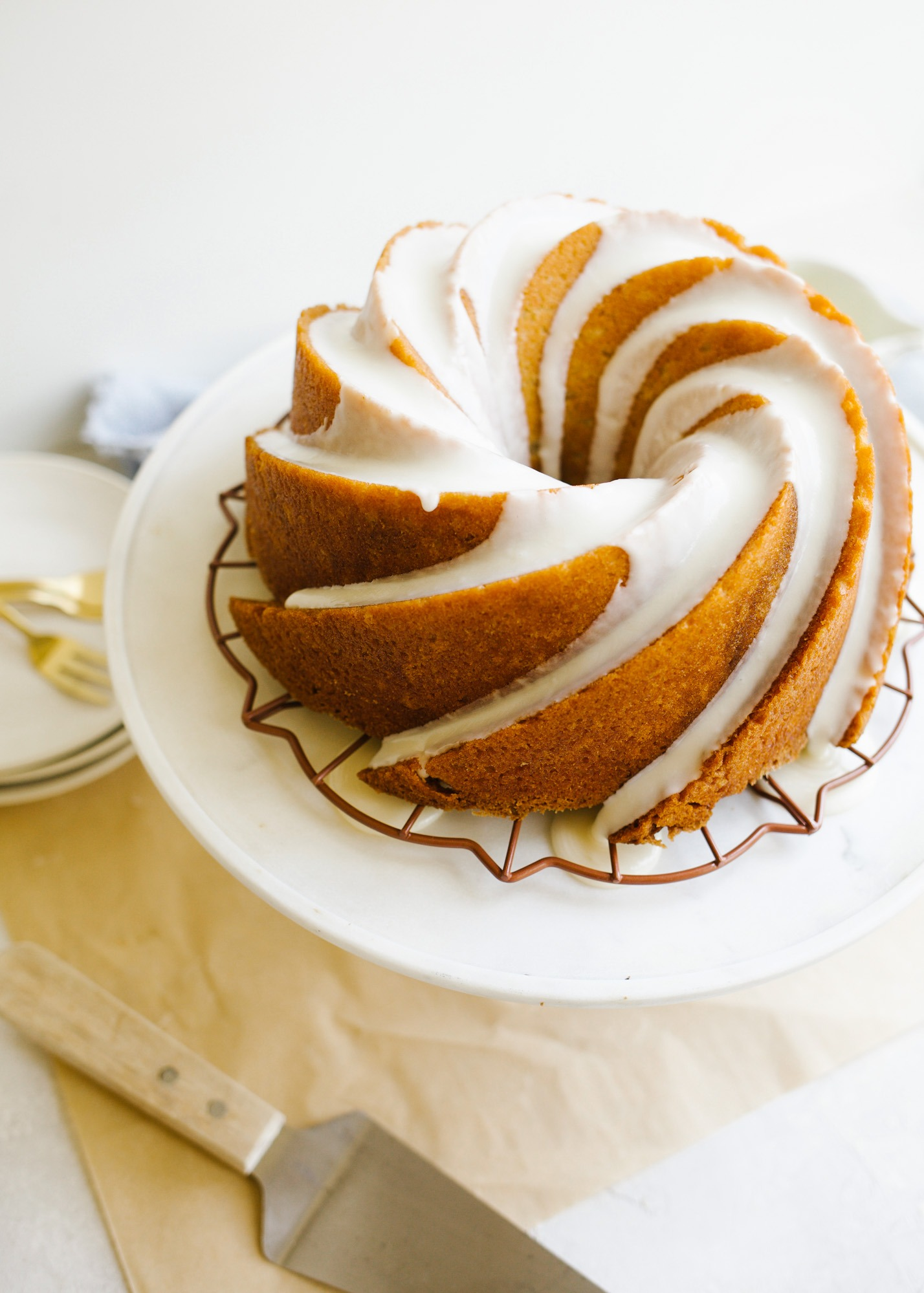 Bourbon Bundt Cake by Kate Wood. This is a boozy and moist bundt cake make with Kentucky whiskey and a bourbon glaze. The cake is fluffy and tall and serves as a great breakfast or brunch or dessert item! It comes together in one bowl and can be made in advance. Learn more about this fall simple cake on thewoodandspoon.com