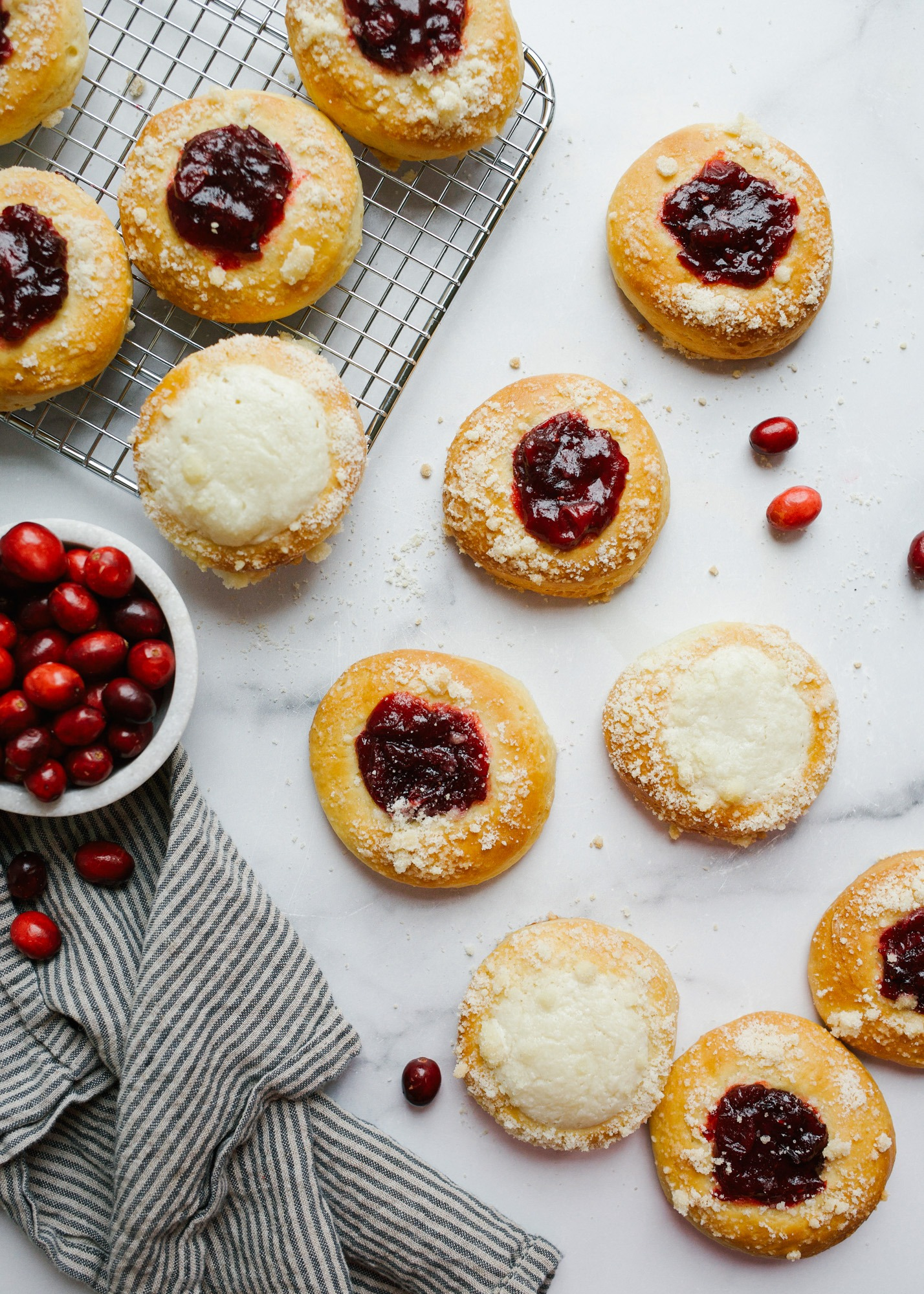 Cranberry Kolaches by Wood and Spoonn blog. These are little puffy sweat yeast parties filled with a homemade cinnamon and cranberry jam or sugared cream cheese filling. Each bite has a little simple crumble on top and is a great breakfast brunch or dessert option. Learn more about the recipe on thewoodandspoon.com.