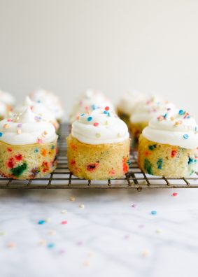 Funfetti Mini Cakes by Wood and Spoon. These are two bite sprinkle cakes, almost like mini cupcakes, made in a mini cheesecake pan. The topping is a light and fluffy whipped cream frosting and the cake taste of nostalgic box birthday cake mix flavor! Learn more about how to make this recipe on thewoodandspoon.com