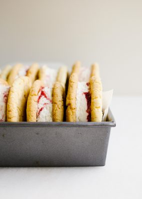 Sugar Cookie Ice Cream Sandwiches with Raspberry Ripple Ice Cream by Wood and Spoon blog. This is Sarah Keiffer's recipe for chewy sugar cookies loaded with no-sugar raspberry swirl ice cream. The ice cream is simple to put together and requires no ice cream machine. These are delicious frozen desserts! Makes enough jumbo treats to share with a crowd and is perfect for summer days! Find the recipe on thewoodandspoon.com