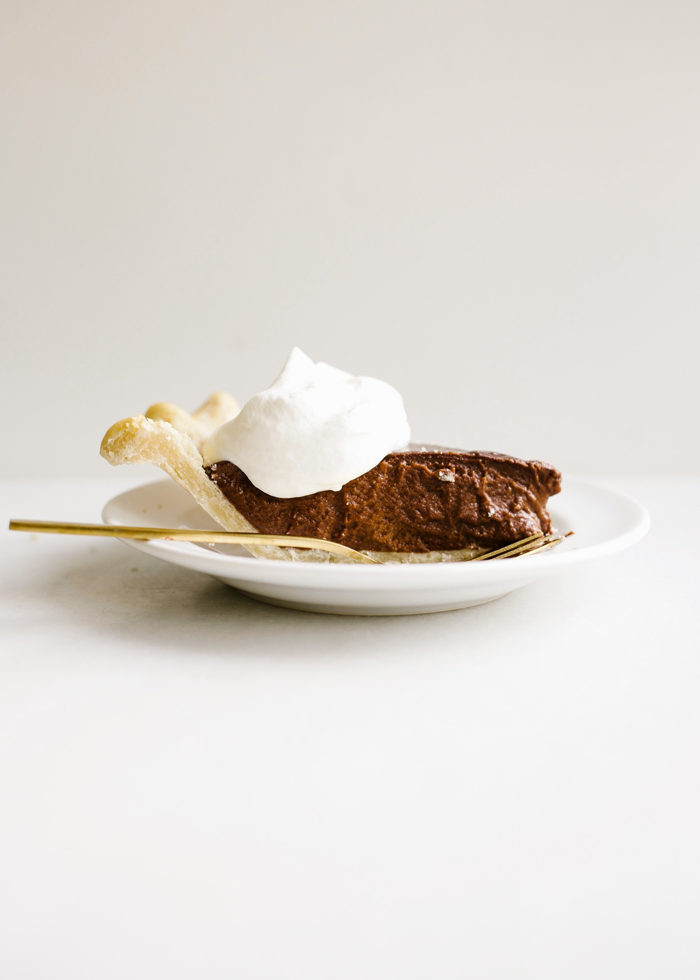 Chocolate Pudding Pie by Wood and Spoon blog. This is an old fashioned Southern chocolate cream pie with a flaky butter and shortening homemade pie crust and an egg custard filling made with cocoa powder! This is a stovetop pie that is a simple treat for a crowd all year round. Chocolate lovers will enjoy this rich dessert on thewoodandspoon.com