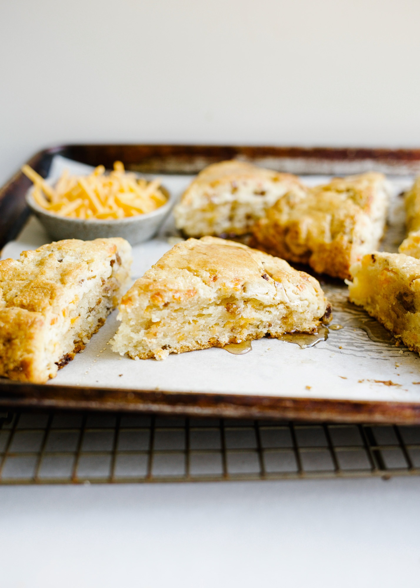 Cheddar Sausage Scones By Wood and Spoon blog. These are simple cream and butter scones sweetened with maple syrup and loaded with Italian sausage, cheddar cheese, and black pepper. These make for a delicious savory breakfast pastry or option for the meat lovers at your table. Learn how to make simple scones for brunch on thewoodandspoon.com