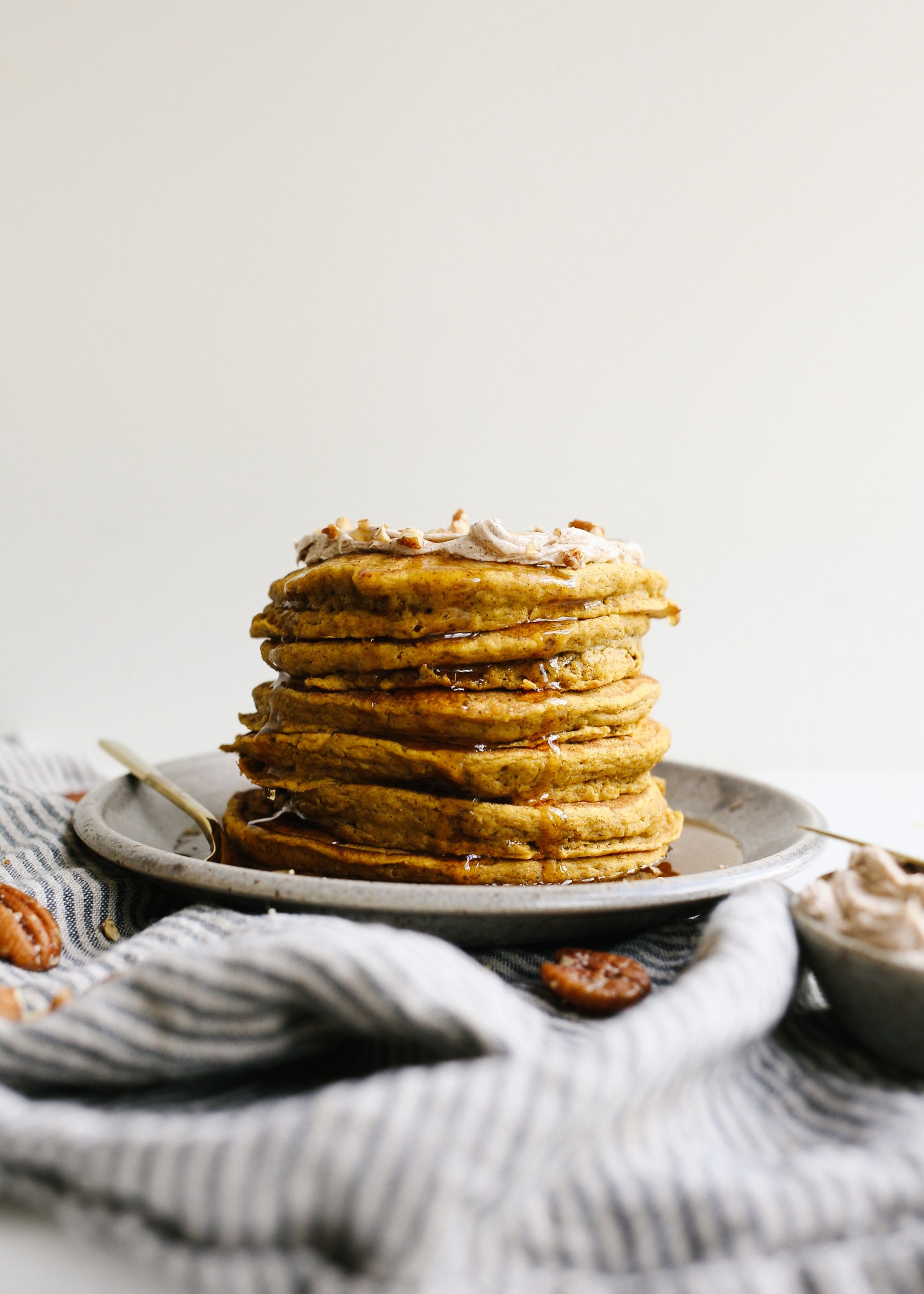 Pumpkin Pancakes with Whipped Cinnamon Butter by Wood and Spoon blog by Kate Wood. These are fluffy pancakes flavored with cinnamon and pumpkin puree. The pancakes are soft and tender and the butter is barely sweetened and scented with spice! Learn how simple these breakfast treats are to make this fall on thewoodandspoon.com