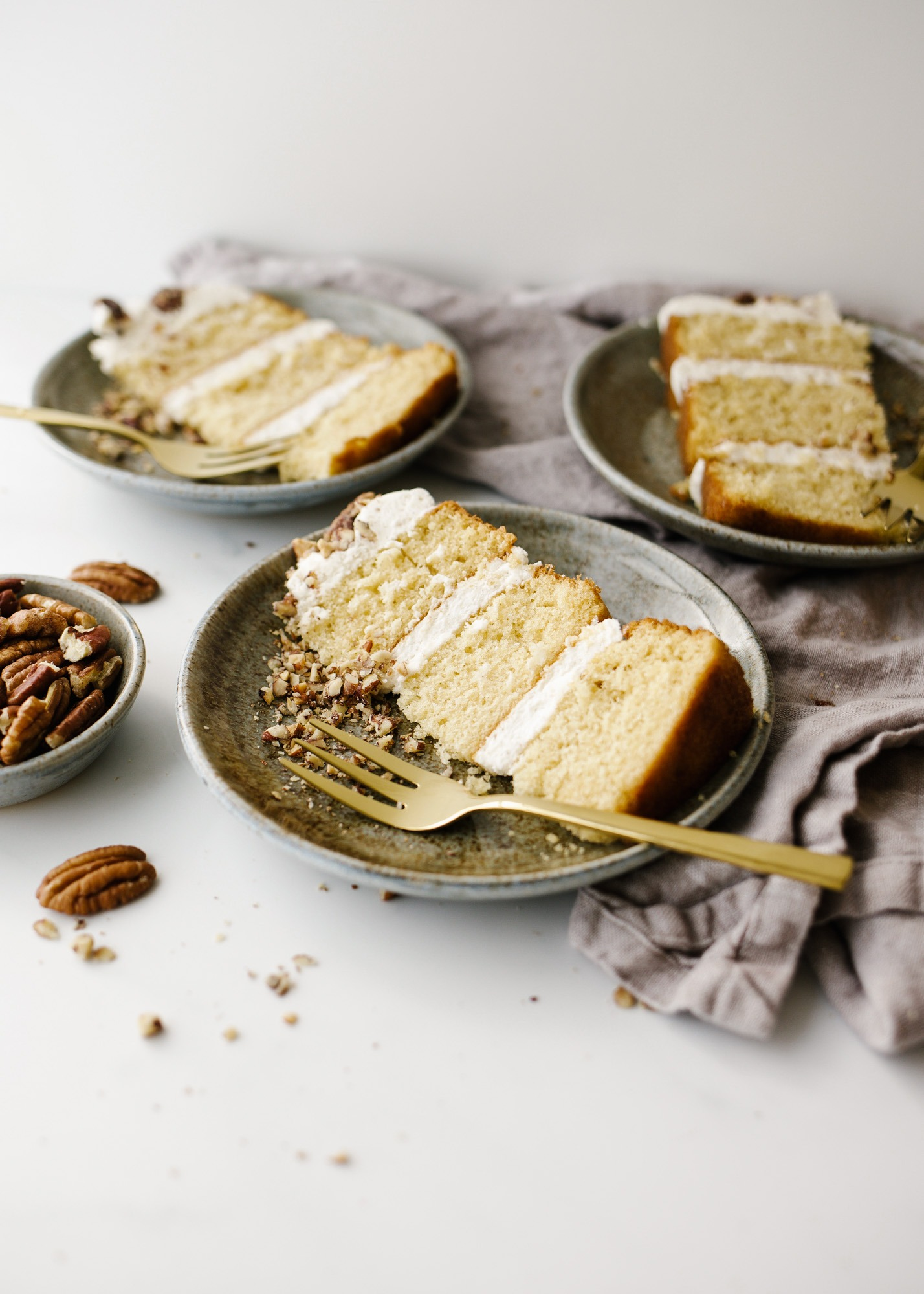 Brown Butter Cake with Candied Pecans by Wood and Spoon blog. This is a simple brown sugar mini layer cake with brown butter buttercream and candied pecans throughout. This small batch recipe makes a small layer cake to serve just a few and makes for a festive offering for fall, winter, and holiday celebration desserts. Learn how to candy nuts and stack a naked layer cake on thewoodandspoon.com