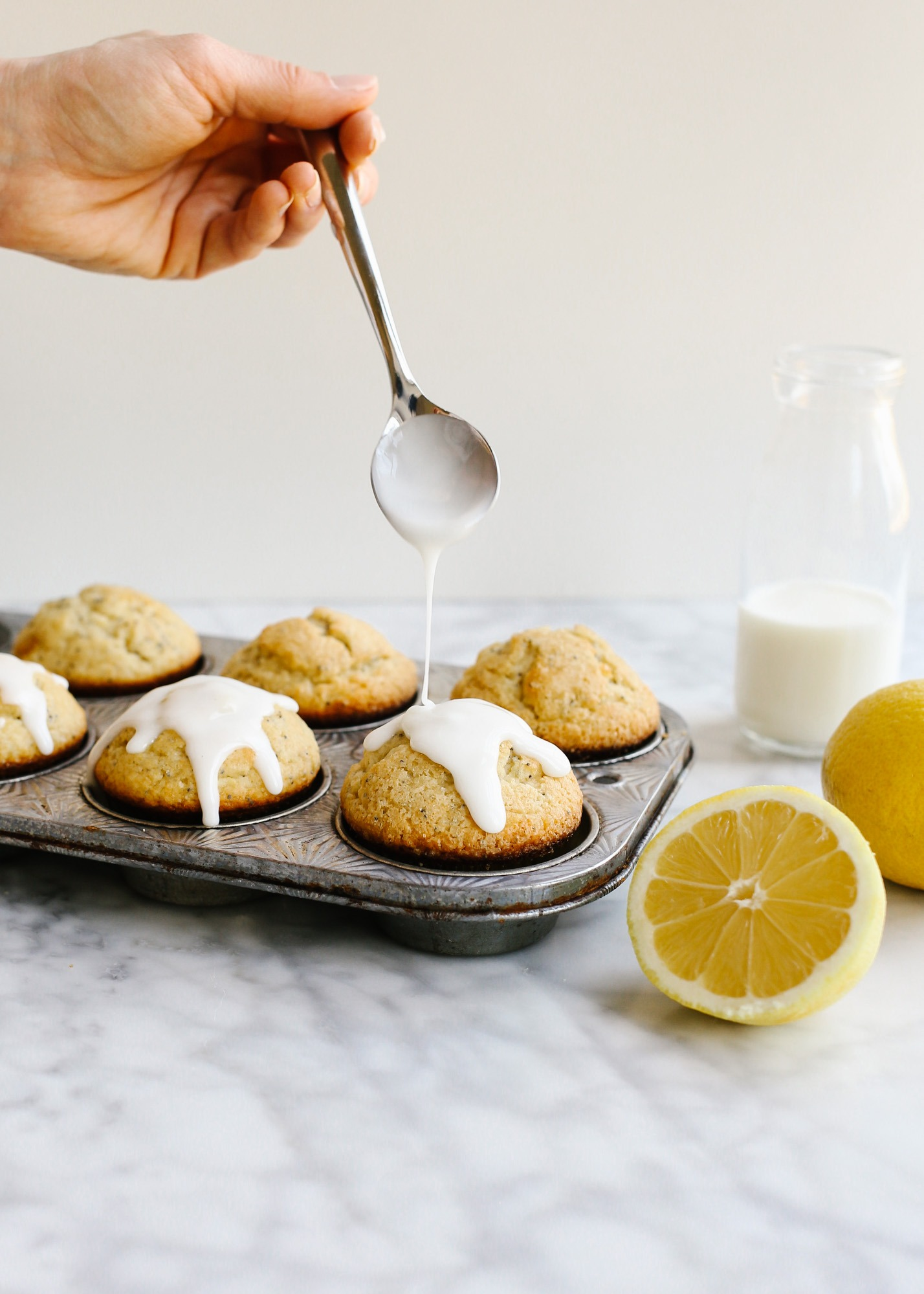 Lemon Poppy Seed Muffins by Wood and Spoon blog. These are light and fluffy homemade butter muffins scented with fresh lemon zest and juice. Poppy seeds throughout add flavor and texture and a simple confectioner's sugar glaze icing on top adds extra sweet and tang. Learn how to make these easy breakfast and brunch treats for a crowd on thewoodandspoon.com