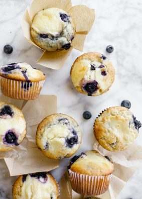 Blueberry Cream Cheese Muffins by Wood and Spoon blog. These are soft and fluffy blueberry muffins swirled with a tangy cream cheese filling. These breakfast pastries make for an interesting spin on the normal morning muffin and taste delicious served warm! Learn how simple it is to make these butter muffins on thewoodandspoon.com