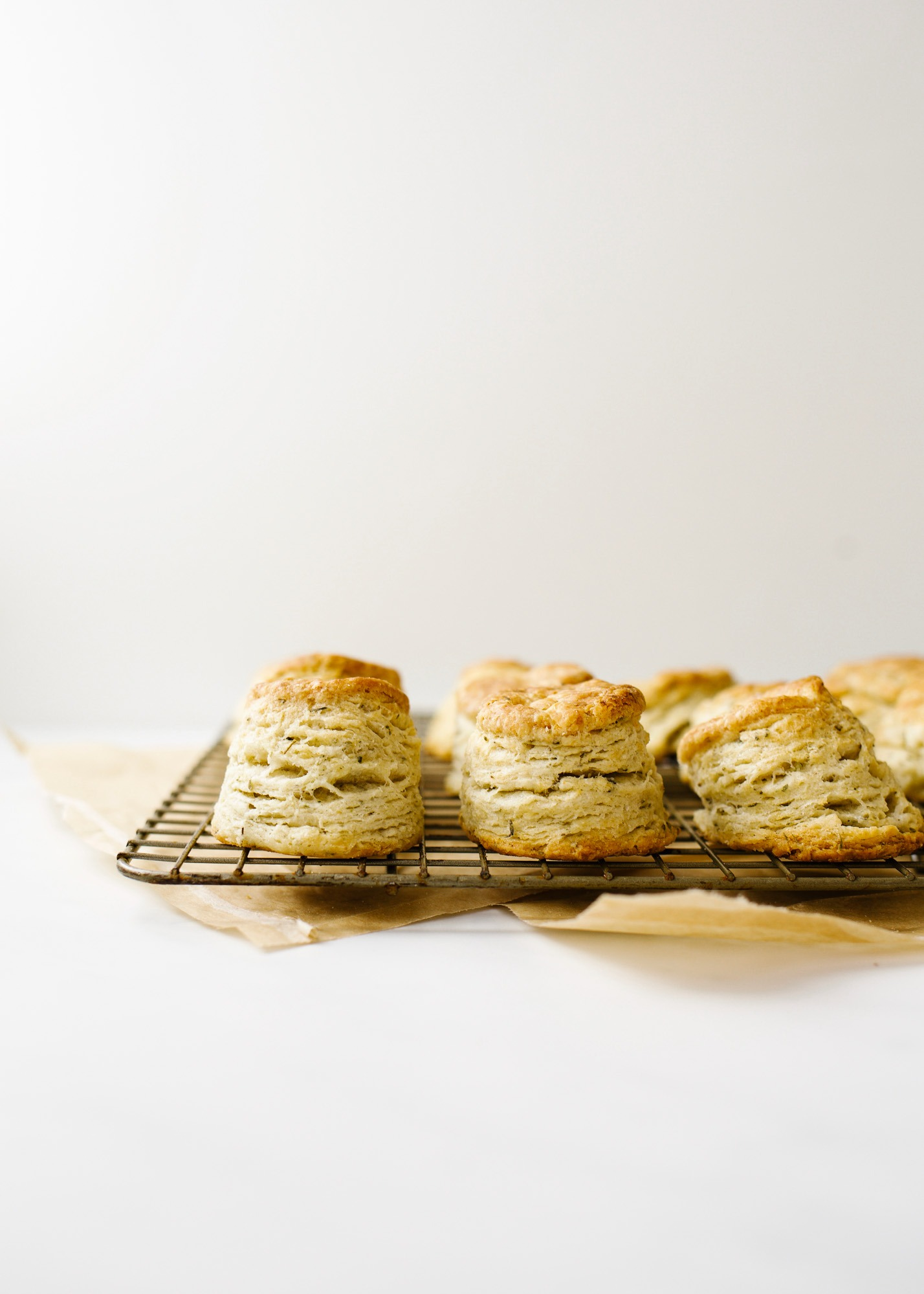 Mini Garlic Herb Biscuits by Wood and Spoon blog. These are bite-sized southern style biscuits layered with garlic, herbs, and loads of butter. These breakfast breads make a great side option for suppers but can also be used as a base for breakfast sandwiches and more! Learn how simple it is to make them on thewoodandspoon.com