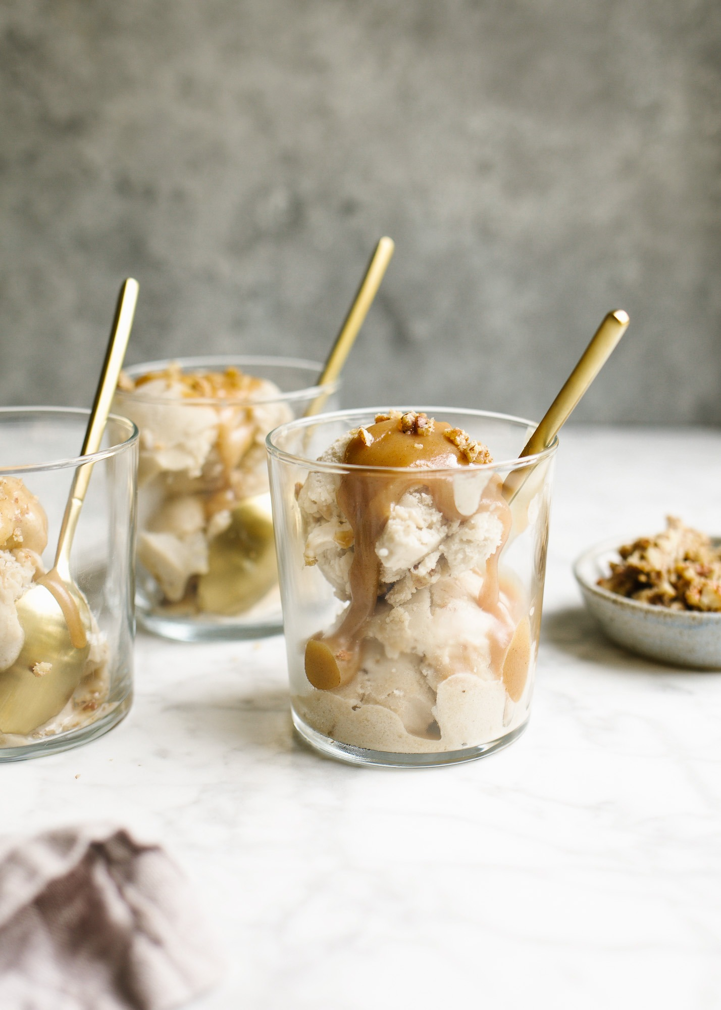 No-Churn Bananas Foster Ice Cream by Wood and Spoon blog. This is a one ingredient ice cream made with frozen bananas, all gussied up with the addition of a rum foster sauce and praline pecans. The ice cream comes together in a blender and is swirled with the stovetop bananas foster sauce and candied nuts. Learn how simple this nice cream is (with options for dairy free ice cream!) on thewoodandspoon.com.