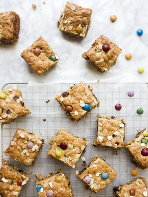 Monster Cookie Bars by Wood and Spoon blog. These chewy peanut butter oatmeal chocolate chip bars are studded with chocolate candies. These make the perfect treats for leftover candy and can be made with almond or peanut butter! Learn how simple these dessert bars are on thewoodandspoon.com.