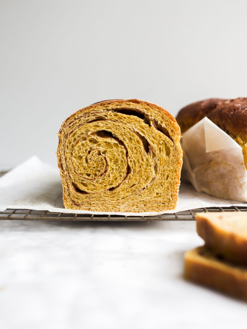 Pumpkin Swirl Bread by Wood and Spoon blog. This is a fluffy pumpkin yeast bread swirled with brown sugar and cinnamon and pumpkin pie spice. The bread is fragrant and works wonderfully for morning toast. Learn how to make a fall sandwich or yeast bread and how simple it is to add sugar to bread dough on thewoodandspoon.com